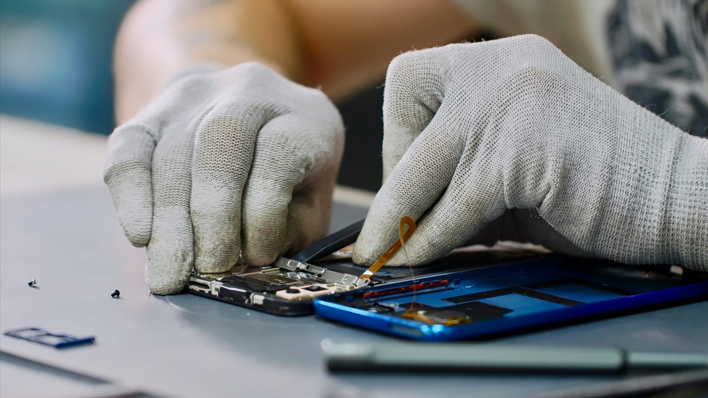 tech hands working on smartphone replacing parts refurbished