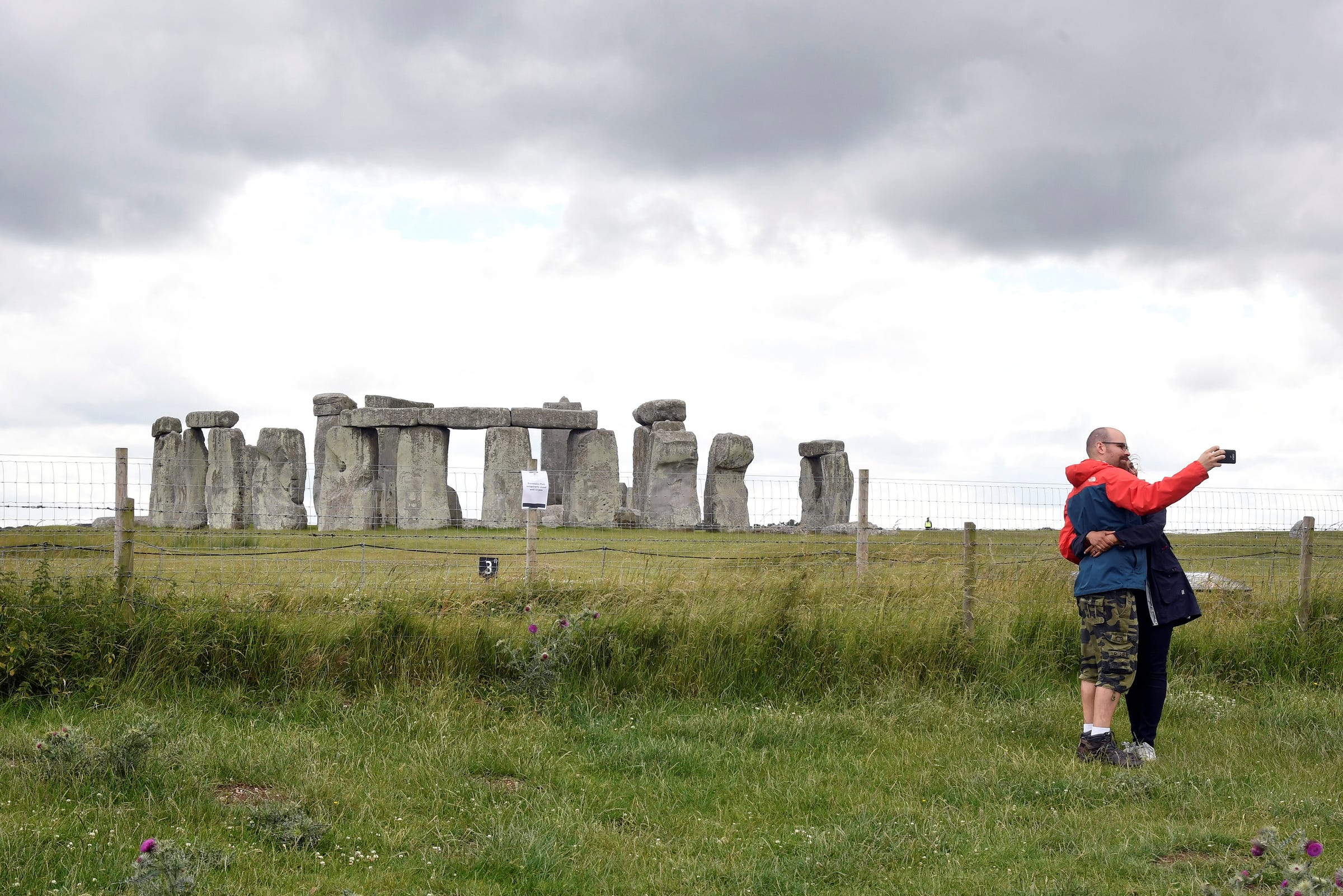 FILE PHOTO: A couple take a selfie as they pass near by the Stonehenge stone circle, where official Summer Solstice celebrations were cancelled due to the spread of the coronavirus disease (COVID-19), near Amesbury, Britain June 20, 2020. REUTERS/Toby Melville