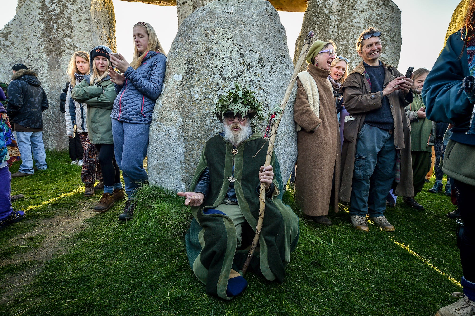 A druid rests in the stone circle at Stonehenge where people gather to celebrate the dawn of the longest day in the UK
