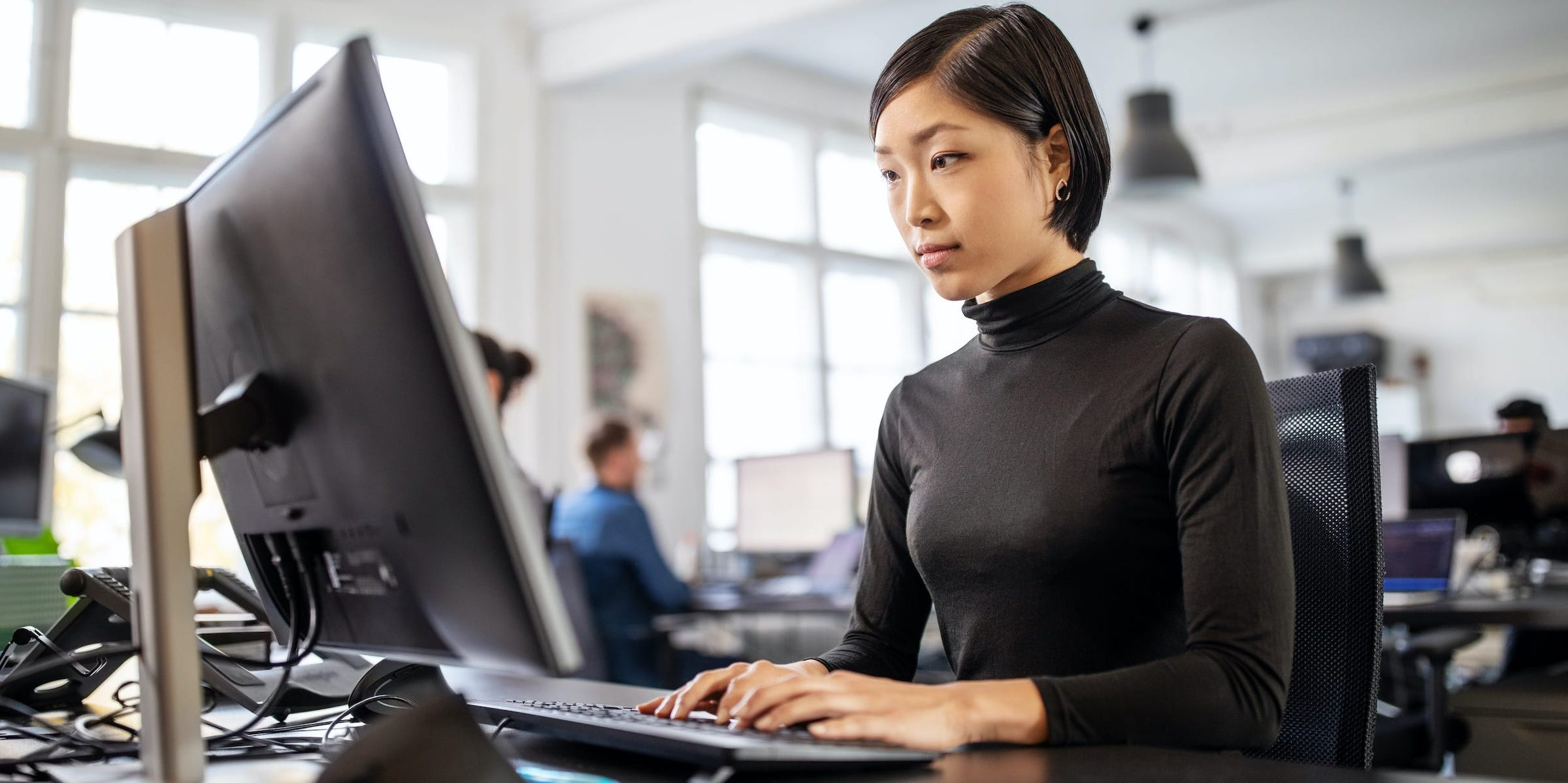 business professional in office typing on desktop computer
